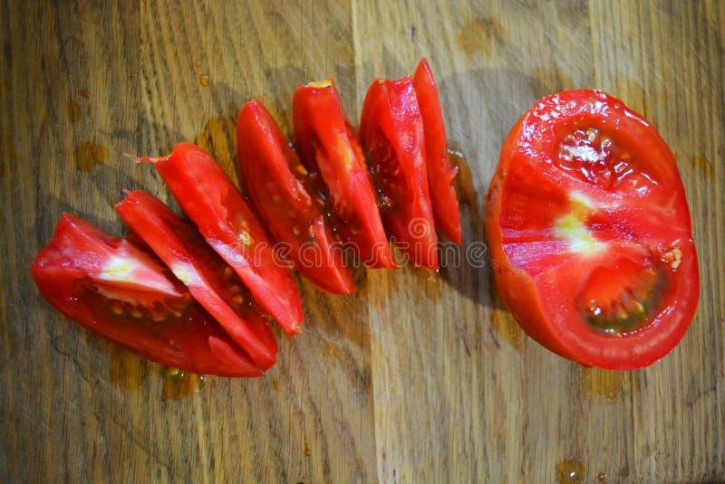 Heldere verse gesneden plakken en de helft van rode tomaat op een houten bruine chef-kokplank royalty-vrije stock afbeeldingen