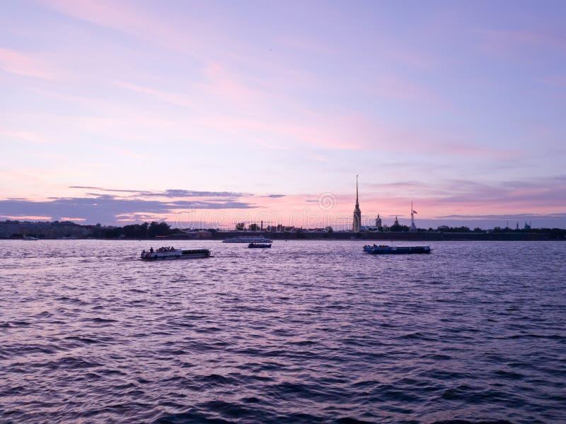 Heldere violet-purpere zonsondergang in de stad van St. Petersburg door de rivier Neva met mening over Peter en van Paul vesting  stock fotografie