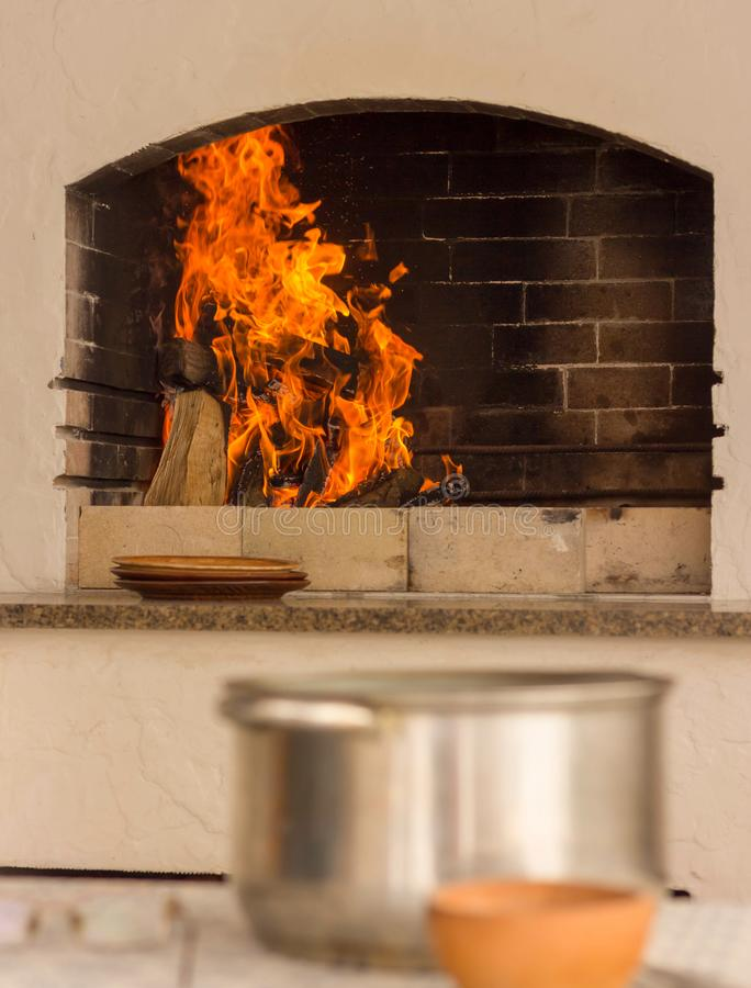 Heldere vlam in de barbecue In de voorgrond is een lijst met huishoudenwerktuigen Het diner zal spoedig klaar zijn stock afbeeldingen