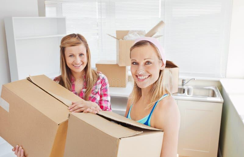 Heldere vrouwelijke vrienden die dozen houden stock afbeeldingen