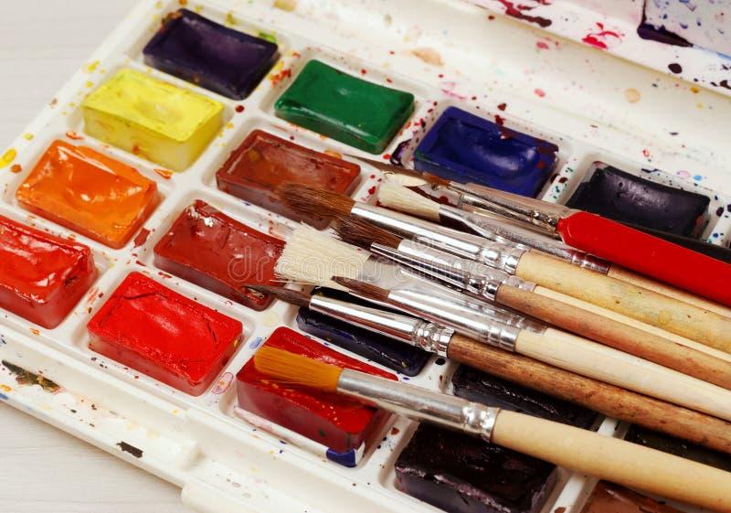 Heldere waterverfverven en gebruikte borstels voor het schilderen Close-up royalty-vrije stock afbeelding