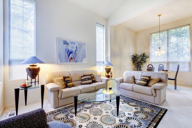Heldere witte en blauwe woonkamer met glaskoffietafel en ru royalty-vrije stock afbeeldingen