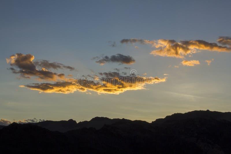 Heldere witte geeloranje wolken in een zonsondergang donkerblauwe hemel over de zwarte silhouetten van de bergen royalty-vrije stock foto