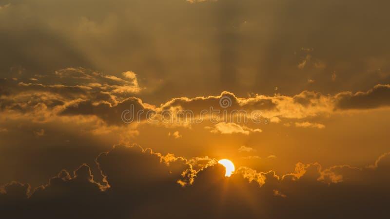 Heldere zon in een oranje hemel met donkere wolken bij zonsondergang royalty-vrije stock afbeelding