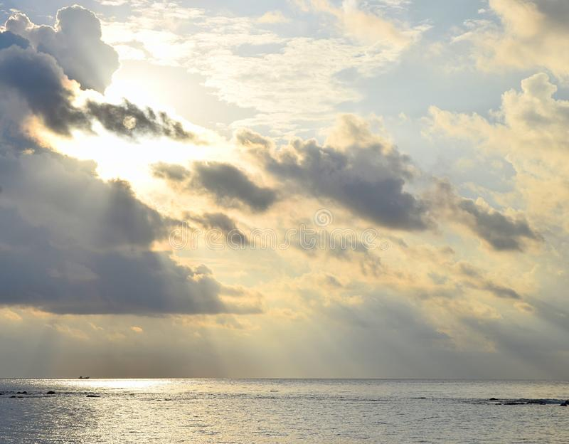 Heldere Zonnestralen van Gouden Gele Zon achter Donkere Wolken en het Uitspreiden over nog Zeewater - Afdaling van Goddelijke Zeg royalty-vrije stock fotografie