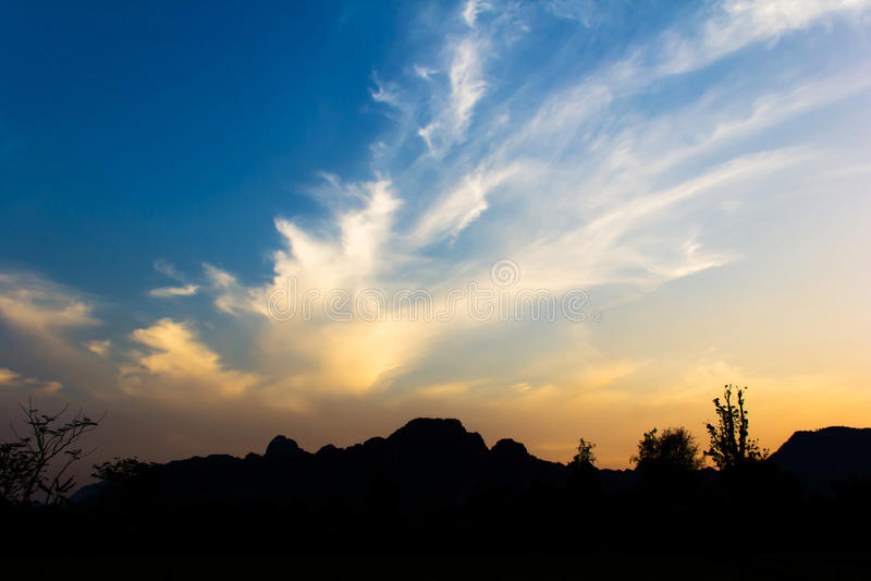 Heldere zonsondergang in hemel over het landschap van Vang Vieng stock foto