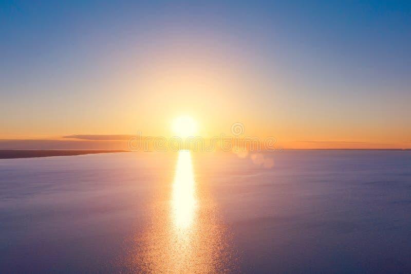 Heldere zonsondergang met gele zon onder de overzeese oppervlakte stock afbeelding