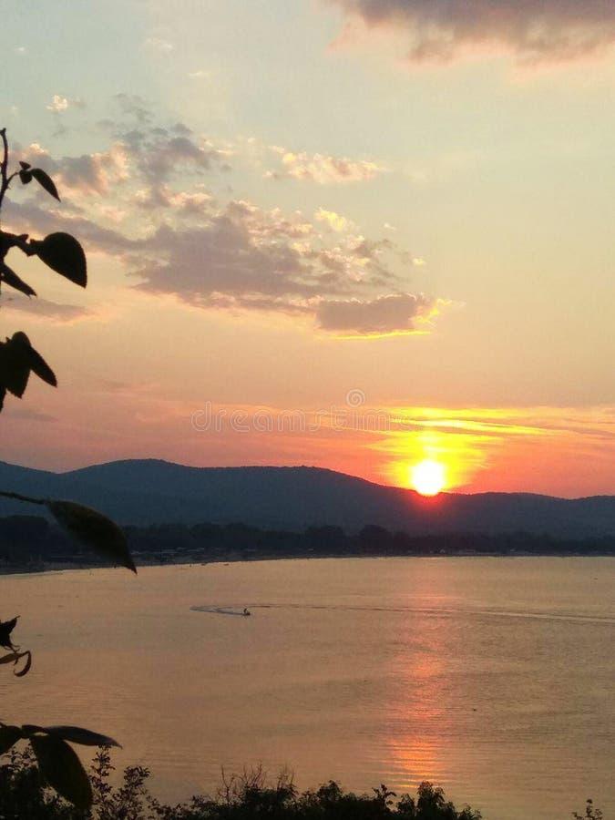 Heldere zonsondergang met grote gele zon onder de overzeese oppervlakte royalty-vrije stock foto's