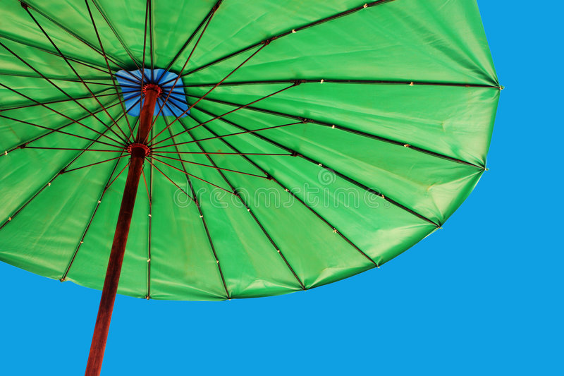 Heldergroene paraplu tegen een blauwe hemel stock foto's