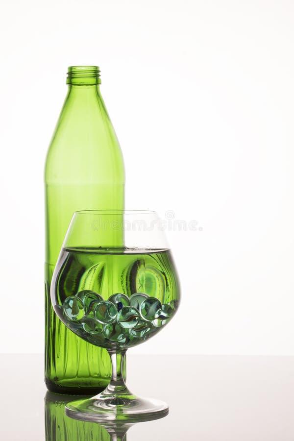 Heldergroene patronen in een glas met vloeistof op een grijze achtergrond royalty-vrije stock fotografie