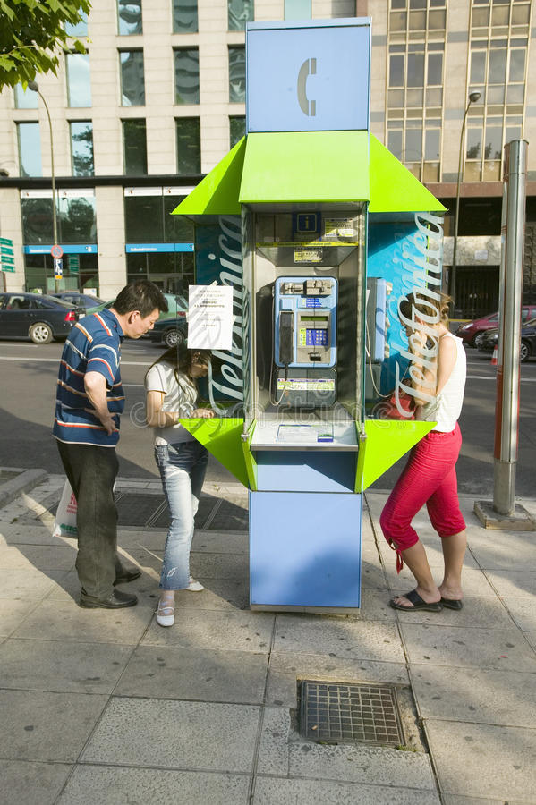 Heldergroene telefooncel die op de de zomerstoepen worden gebruikt van Madrid, Spanje stock fotografie