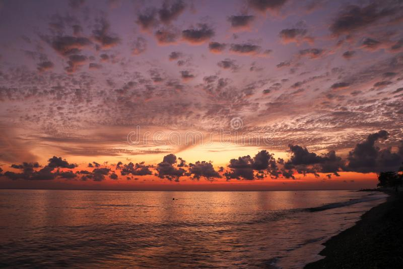Helderoranje en gele zonnehemel. Zonnestijging met wolken, lichtstralen en ander atmosferisch effect royalty-vrije stock foto's