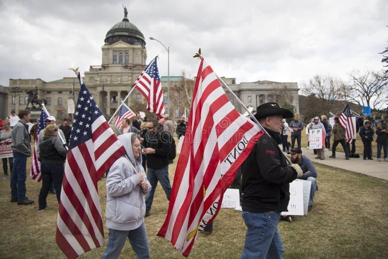 Helena, Montana - 19 april 2020: Demonstranter, en man och en kvinna, med amerikanska flaggor som marscherar mot en protest mot arkivbilder