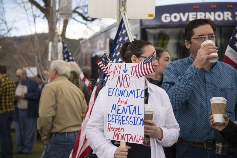 Helena, Montana - 19 april 2020: En kvinna som protesterar mot ekonomiska och psykiska depressioner i en demonstration i arkivbild