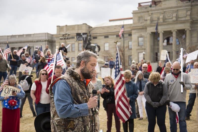 Helena, Montana - 19 april 2020: En man som talar och ber om en protestfrihet samlas på Capitol igen efter stängningen på grund a royaltyfria foton
