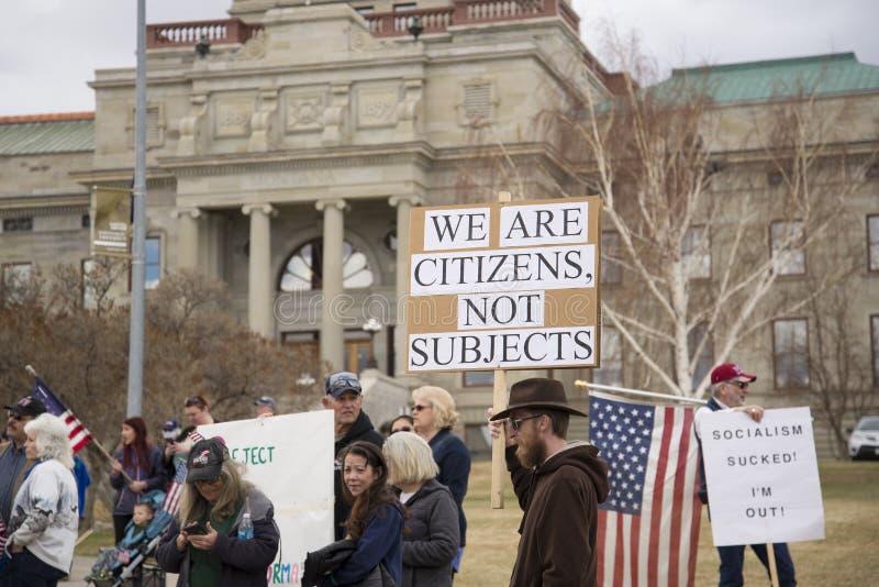 Helena, Montana - 19 april 2020: En protestantisk man har ett tecken vid ett möte i Capitol mot regeringens stängning Vill arkivfoto