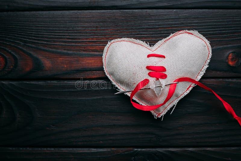 Helend gebroken hart Naald met een rood lint die een stof h naaien stock foto's
