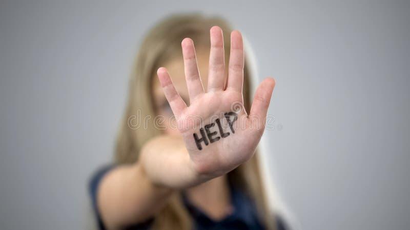 Helfen Sie Aufschrift auf Palme des traurigen kleinen Mädchens, Schutz der Rechte der Kinder lizenzfreies stockbild