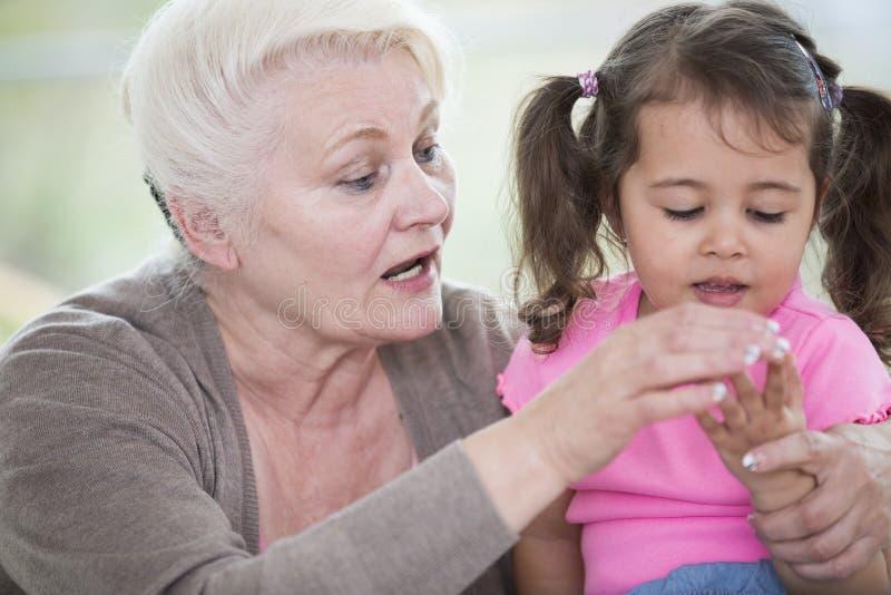Helfende Enkelin der älteren Frau, wenn zu Hause Finger gezählt werden lizenzfreies stockbild