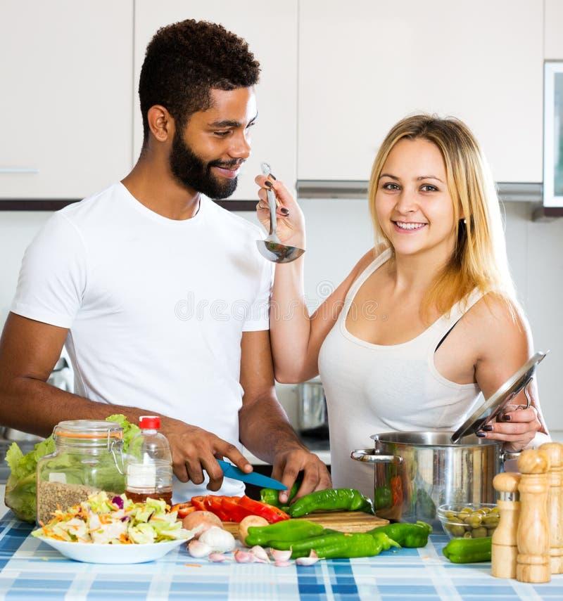 Helfende Frau des Ehemanns, die gesundes Abendessen vorbereitet lizenzfreie stockbilder