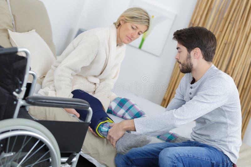 Helfende Frau des jungen Mannes, zum des verletzten Beines zu bewegen lizenzfreies stockbild