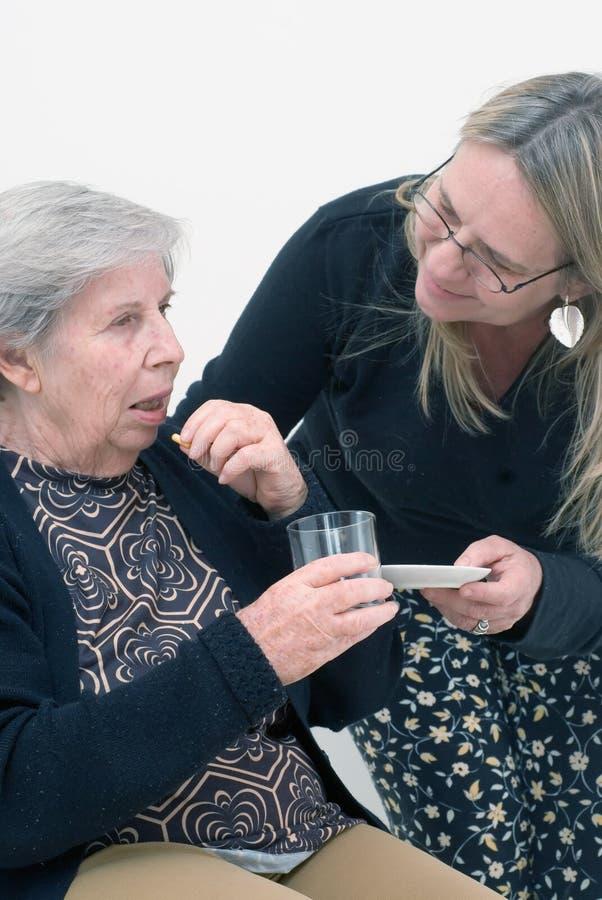 Helfende Großmutter mit ihrer Medikation stockfotografie