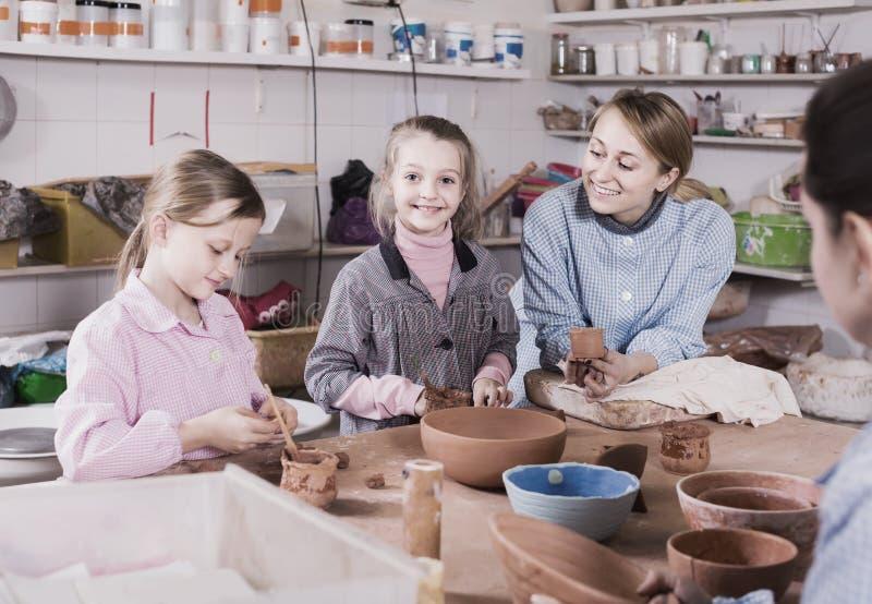 Helfende Jugendliche des Lehrers an der Herstellung von Tonwaren während der Künste und des craf lizenzfreie stockfotos