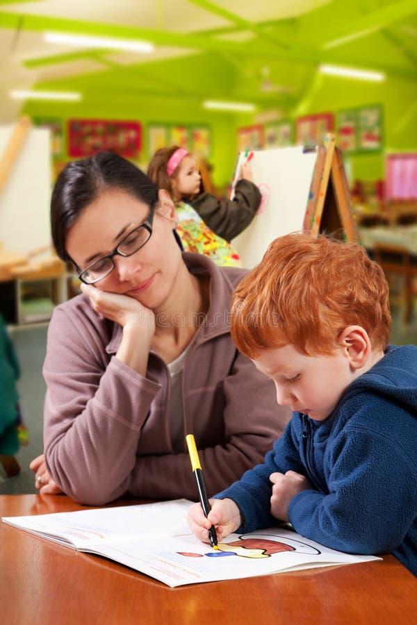 Helfende Kinder des Kindergartenvorschullehrers stockbild