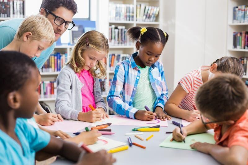 Helfende Kinder des Lehrers mit ihrer Hausarbeit in der Bibliothek lizenzfreie stockfotos