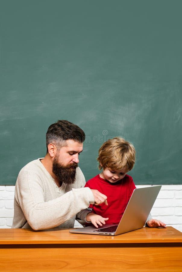 Helfende Kinder des Lehrers mit ihrer Hausarbeit im Klassenzimmer in der Schule homeschooling Mannlehrerspiel mit Vorsch?lerkind stockbild