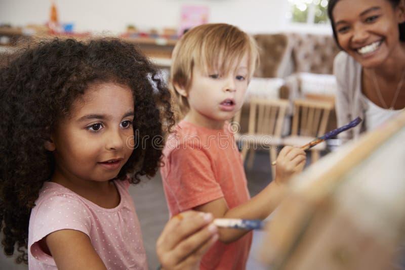 Helfende Kinder Lehrer-At Montessori Schools in Art Class lizenzfreie stockfotos