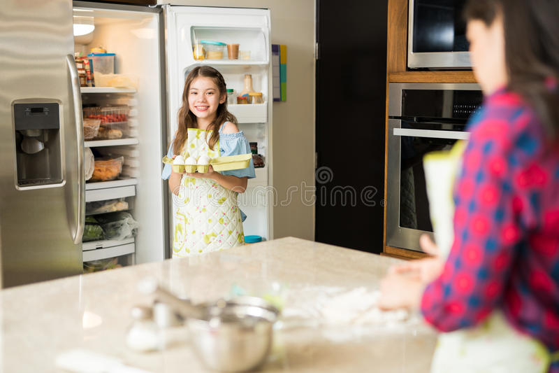 Helfende Mutter der Tochter in der Küche lizenzfreie stockbilder