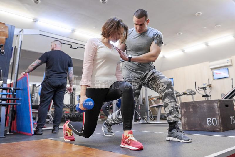Helfende Sommerfrau des persönlichen Eignungslehrers, die im Fitnessstudio trainiert Gesundheitseignungssport-Alterskonzept stockbild