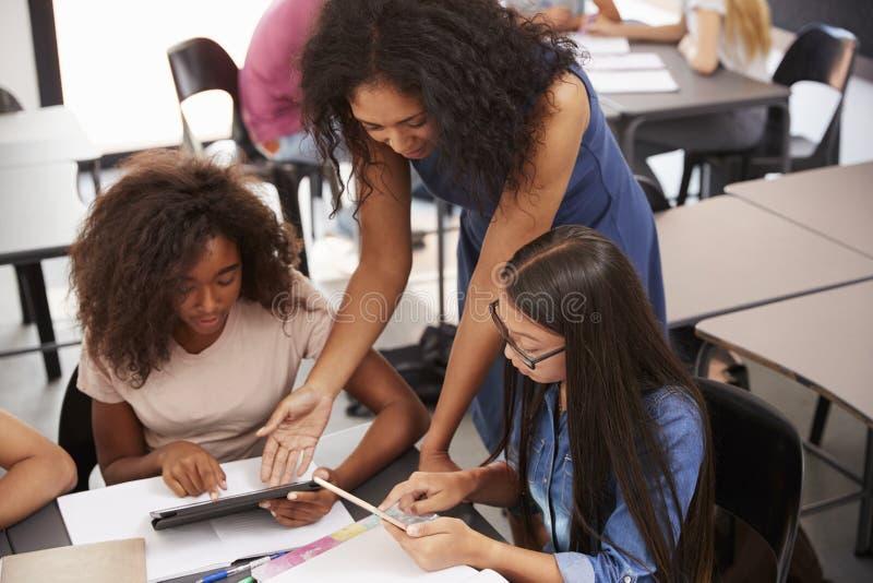 Helfende Studenten des Lehrers mit Technologie, hoher Winkel stockfotos