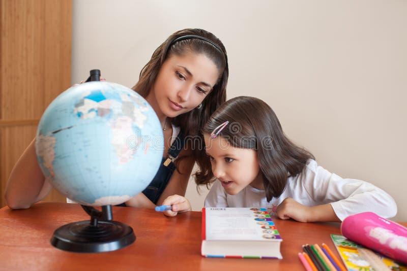 Helfende Tochter der Mutter mit Hausarbeit lizenzfreie stockfotos