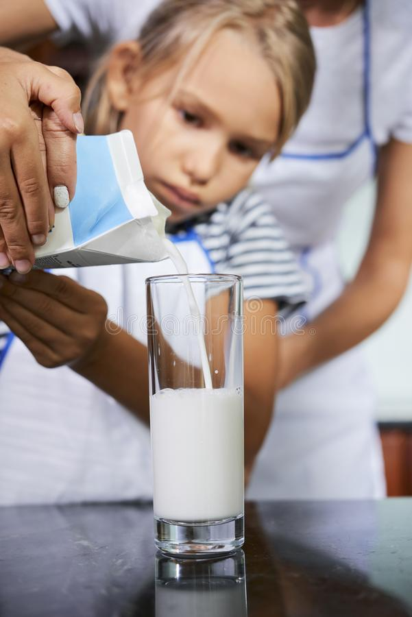 Helfende Tochter der Mutter, zum des Glases mit Milch zu füllen lizenzfreies stockfoto