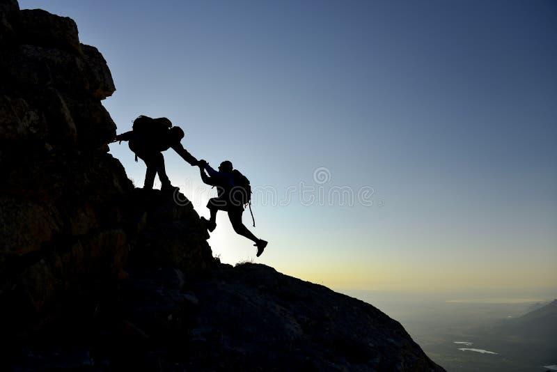 Helfender Freund des Bergsteigers auf Bergabhang stockfotografie