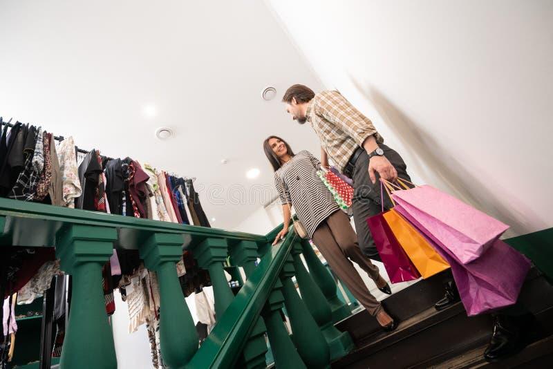 Helfender interessierender netter erwachsener Mann, der Dame mit Einkaufstaschen unterstützt lizenzfreies stockfoto