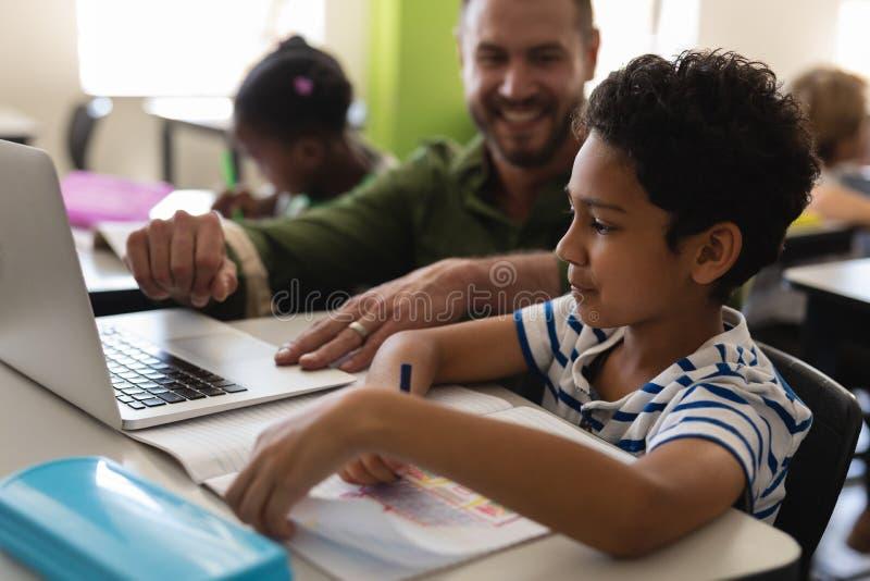 Helfender Junge des jungen Schullehrers mit Untersuchung über Laptop im Klassenzimmer lizenzfreie stockbilder