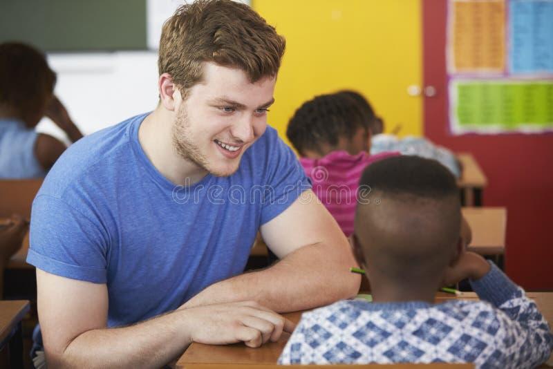 Helfender Junge des weißen Mannfreiwillig-Lehrers in der grundlegenden Schulklasse stockfoto