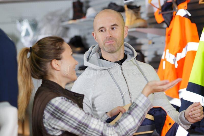 Helfender Kunde des weiblichen Verkäufers, zum der Arbeitskleidung zu wählen lizenzfreies stockfoto