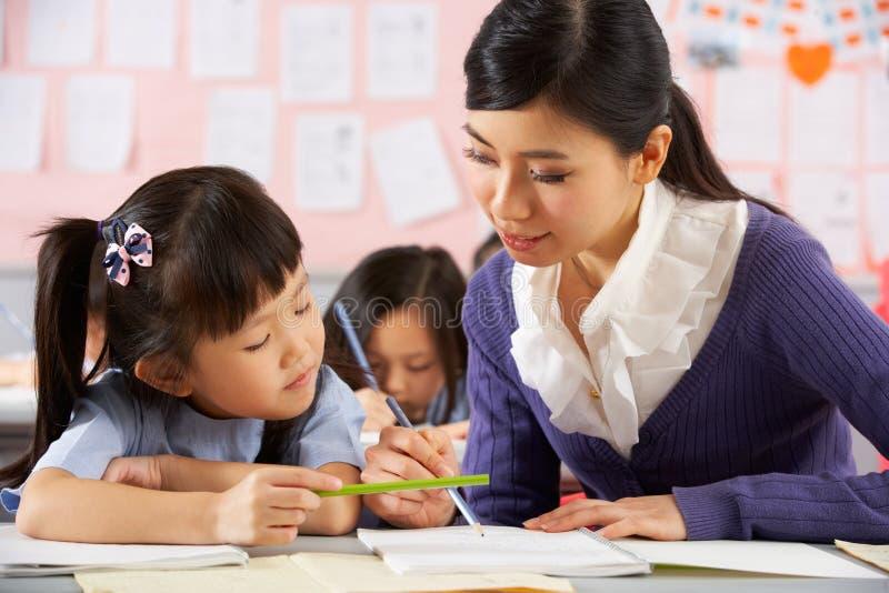 Download Helfender Kursteilnehmer, Der Am Schreibtisch In Der Chinesischen Schule Arbeitet Stockfoto - Bild von leute, hong: 26363338