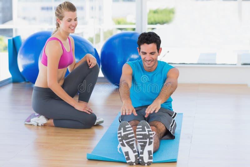 Helfender Mann des weiblichen Trainers mit seinen Übungen an der Turnhalle stockfoto