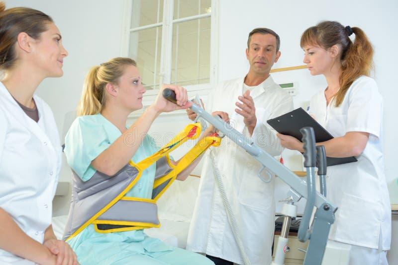 Helfender Patient des medizinischen Personals, zum sich vom Bett anzuheben lizenzfreie stockbilder