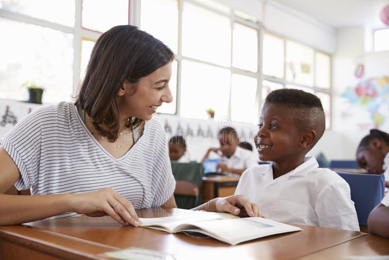 Helfender Schüler des freiwilligen Lehrers an seinem Schreibtisch, Abschluss oben lizenzfreie stockfotografie
