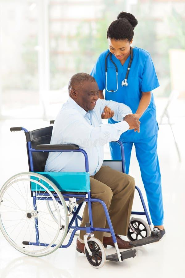 Helfender Senior der afrikanischen Pflegekraft stockbilder