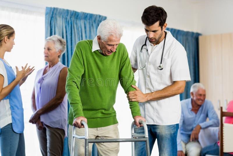 Helfender Senior der Krankenschwester mit Gehhilfe lizenzfreies stockfoto