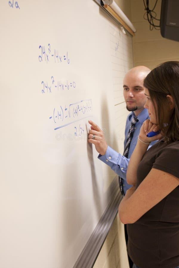 Helfender Student des Lehrers mit einem mathematischen Problem auf einem whiteboard. lizenzfreie stockfotografie