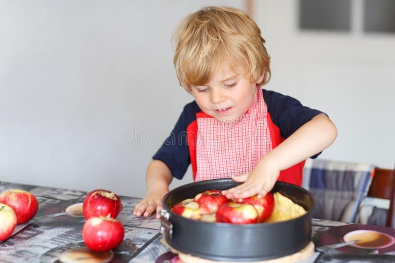 Helfender und backender Apfelkuchen des entzückenden kleinen Jungen in Haupt'' s-kitc lizenzfreies stockbild