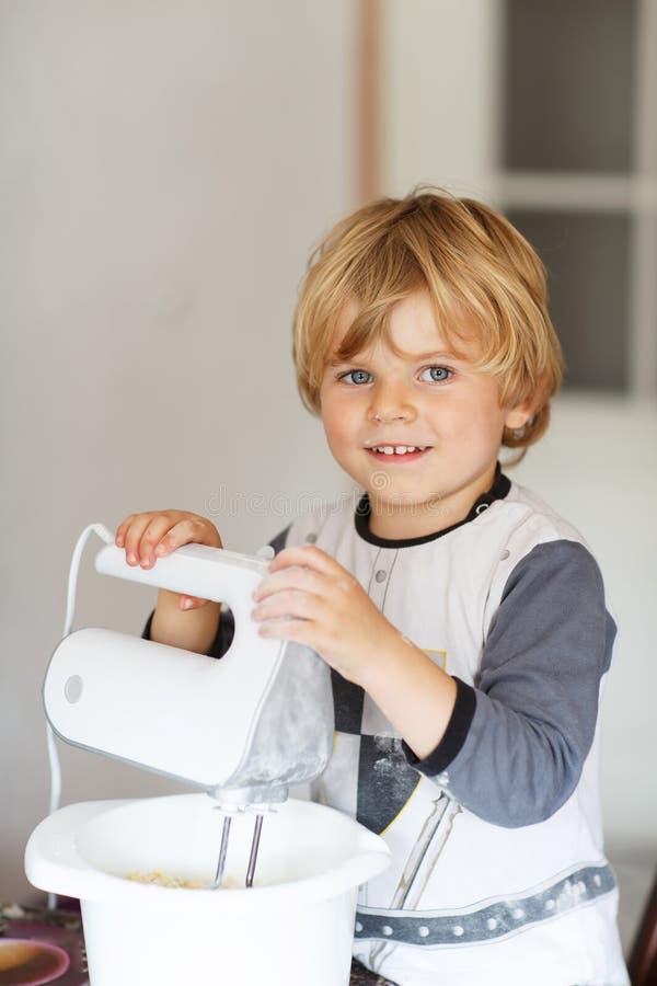 Helfender und backender Apfelkuchen des entzückenden kleinen Jungen in Haupt'' s-kitc stockfoto